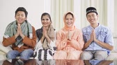 pakistani : Group of attractive young muslim people showing a greeting hands gesture while smiling at camera and sitting on the sofa at home. Shot in 4k resolution