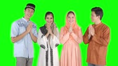 pakistani : Group of young muslim people with greeting hands gesture for forgiving each other in the studio. Shot in 4k resolution with green screen background