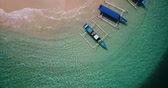 konaklama : Beautiful top down view of boats on the beach with turquoise water and white sand in Gili Nanggu Island at Lombok near Bali, Indonesia. Shot in 4k resolution from a drone flying upwards