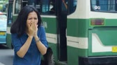 transporte : Air Pollution Concept. Young woman coughing and closing her mouth while standing on the sidewalk. Shot in 4k resolution Stock Footage