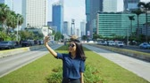 sourire : Young woman making a video call with a mobile phone on the street with Hotel Indonesia Roundabout background in Jakarta city, Indonesia. Shot in 4k resolution