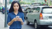transporte : JAKARTA, Indonesia - April 24, 2019: Young woman using a mobile phone while standing on the street in the city. Shot in 4k resolution