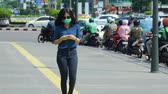transporte : JAKARTA, Indonesia - April 24, 2019: Air Pollution Concept. Young woman wearing a mask while walking on the sidewalk and using a mobile phone. Shot in 4k resolution Stock Footage