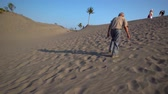 fussspuren : Elderly man climbing sand hill at the Gumuk Pasir park in Yogyakarta, Indonesia. Shot in 4k resolution