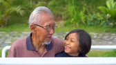 unoka : Happy elderly man talking with his granddaughter while sitting on the swing at the park. Shot in 4k resolution