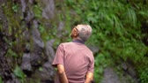 sourire : Happy elderly man with gray hair enjoying waterfall view at the forest. Shot in 4k resolution