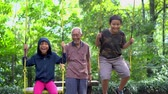 irmãs : Joyful children and their grandfather playing on the swing at the park. Shot in 4k resolution Stock Footage