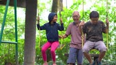 sourire : Cheerful kids playing on the swing with their grandfather at the park. Shot in 4k resolution Vidéos Libres De Droits