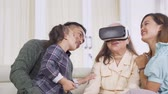 three generation : Happy elderly woman using virtual reality headset with her child and granddaughter while sitting on the sofa at home. Shot in 4k resolution Stock Footage