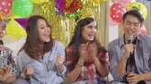 mike : Group of attractive young people having fun together while singing together in a birthday party at home. Shot in 4k resolution Stock Footage