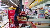 gıda maddeleri : JAKARTA, Indonesia - May 21, 2019: Young female buyer paying her groceries on the cashier in supermarket Stok Video
