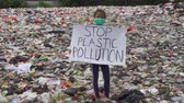sorumluluk : JAKARTA, Indonesia - May 21, 2019: Little girl showing a text of Stop Plastic Pollution while standing on the landfill with plastic waste background. Shot in 4k resolution Stok Video