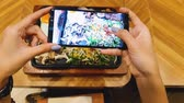 dish photo : Woman hands taking photo of her lunch with smart phone in the restaurant. Shot in 4k resolution