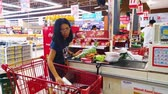 gıda maddeleri : JAKARTA, Indonesia - May 21, 2019: Young woman paying her groceries on the cashier in supermarket Stok Video