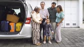 maleta antigua : Happy little girl standing with her parents and grandparents beside the car with luggage for traveling. Shot in 4k resolution Archivo de Video