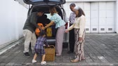 maleta antigua : Cute little girl helping her parents to load luggage into the car trunk for traveling. Shot in 4k resolution Archivo de Video