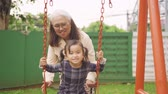 houpavý : Cute little girl playing on the swing with her grandmother at park. Shot in 4k resolution