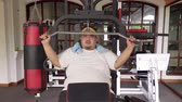 obezita : Overweight man doing workout on weightlifting machine at fitness center. Shot in 4k resolution
