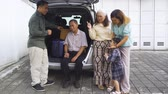 maleta antigua : Happy three generation family preparing luggage for traveling while chatting behind the car. Shot in 4k resolution