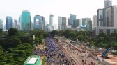 запустить : JAKARTA, Indonesia - May 27, 2019: Aerial view of crowded people enjoy outdoor activities during the car free day at Sudirman street. Shot in 4k resolution from a drone flying forwards
