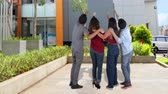 zadnice : Back view of group of college students pointing and looking up outdoors. Shot in 4k resolution