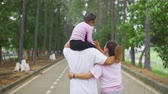 meeliften : Slow motion back view of happy family walking together at the park with father giving daughter piggyback ride on his shoulder Stockvideo