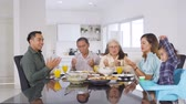 retirement home : Three generation happy muslim family praying together before eating in dining room at home. Shot in 4k resolution
