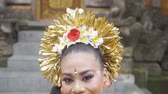 balinese : Closeup of pretty balinese dancer dancing and smiling at the camera in the temple Stock Footage