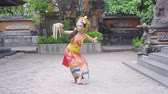 балийский : Beautiful young balinese dancer dancing while carrying frangipani flower in the temple. Shot in 4k resolution