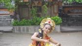 balinese : Slow motion of pretty balinese dancer performing while throwing frangipani flower and wearing traditional costume in the temple Stock Footage