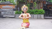 balinese : Slow motion of pretty balinese dancer performing while sitting and throwing frangipani flower in the temple Stock Footage