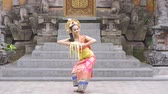 balinese : Beautiful balinese dancer posing in the temple while wearing traditional costume and holding frangipani flower. Shot in 4k resolution Stock Footage