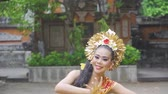 balinese : Slow motion of young balinese dancer performing in the temple while wearing traditional costume and throwing frangipani flower