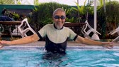 zwemmer : Happy senior man playing in swimming pool while wearing goggles and swimwear. Shot in 4k resolution