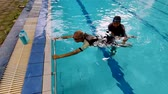 teach : Senior man learns to swim with his son or personal trainer in swimming pool. Shot in 4k resolution Stock Footage