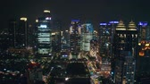fachada : JAKARTA, Indonesia - July 15, 2019: Aerial view of modern office buildings tower and beautiful night lights in business district. Shot in 4k resolution from a drone flying forwards