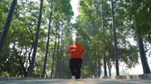 antreman : Low angle of overweight man doing workout by running at the park for losing weight. Shot in 4k resolution Stok Video