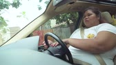 hasábburgonya : Overweight woman driving a car while eating french fries on the road. Shot in 4k resolution