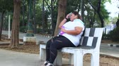 törülköző : Overweight young woman jogging at the park and taking a break while sitting and drinking water on the bench. Shot in 4k resolution