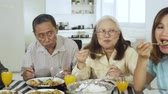 Happy three generation family having lunch together in dining room at home. Shot in 4k resolution