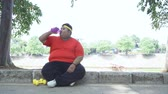 dýchat : Tired obese man drinking a bottle of mineral water while sitting on the pavement after workout at the park. Shot in 4k resolution