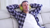 ecouter la musique : Happy caucasian man sitting on sofa while listening music with a wireless headphones in the living room at home. Shot in 4k resolution