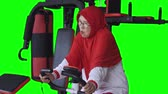 Senior woman doing workout by riding exercise bike. Shot in 4k resolution with green screen background Wideo