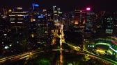 de espaldas : JAKARTA, Indonesia - January 29, 2020: Beautiful aerial view of traffic around the Semanggi Interchange at night time from a drone flying backwards in Jakarta city. Shot in 4k resolution
