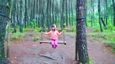 houpavý : Bogor, Indonesia - January 29, 2020: Little girl smiling at the camera while playing on a swing in the pine forest