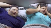 Top view of fat young woman annoyed by her snoring husband while sleeping on the bed. Shot in 4k resolution
