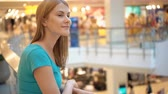 shopaholic : Young beautiful attractive woman standing in shopping mall, smiling. Shopping consumerism concept. Stock Footage
