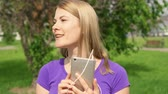 hop garden : Active woman listening music on mobile phone with earphones and singing in park. Using her smartphone, dancing and singing Stock Footage