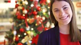 ziyafet : Portrait of cheerful young woman near decorated Christmas tree. Pretty female standing and smiling. New Year celebration Stok Video
