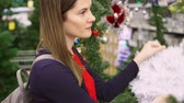 věnec : Woman buying Christmas decorations. Female choosing Christmas wreath. Christmas trees and decorations on background. New Year celebration
